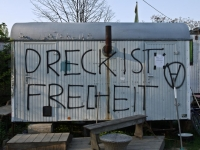 Farbphotographie: Container mit Rauchfang, davor Holzbank